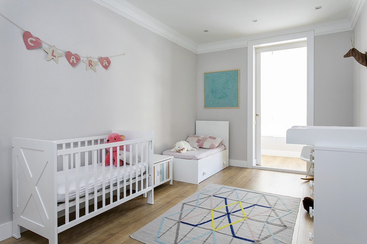 Habitación infantil con una cuna, los muebles para un bebé y decoración infantil. Habitación muy luminosa