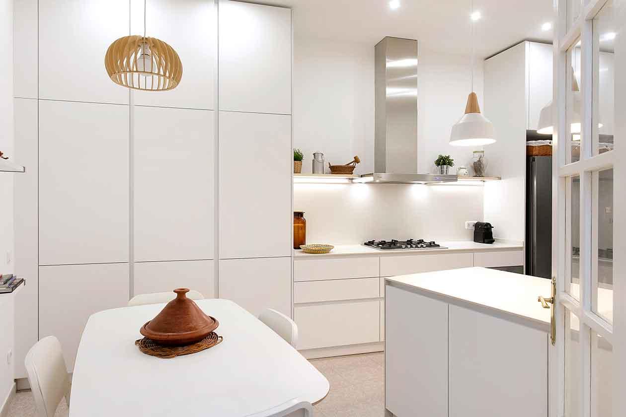Espacio de desayuno con mesa y sullas y la cocina al fondo