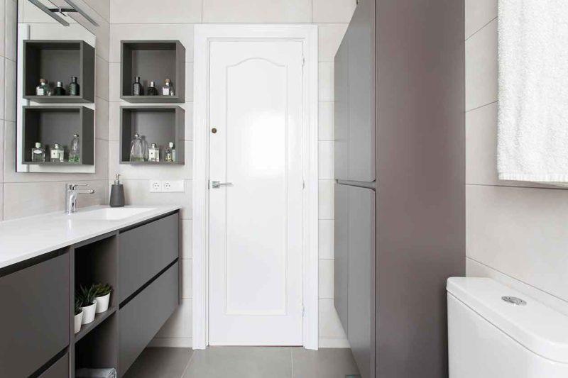 Baño reformado visto des del fondo, con la puerta en frente, armarios a la derecha y las picas a la izquierda