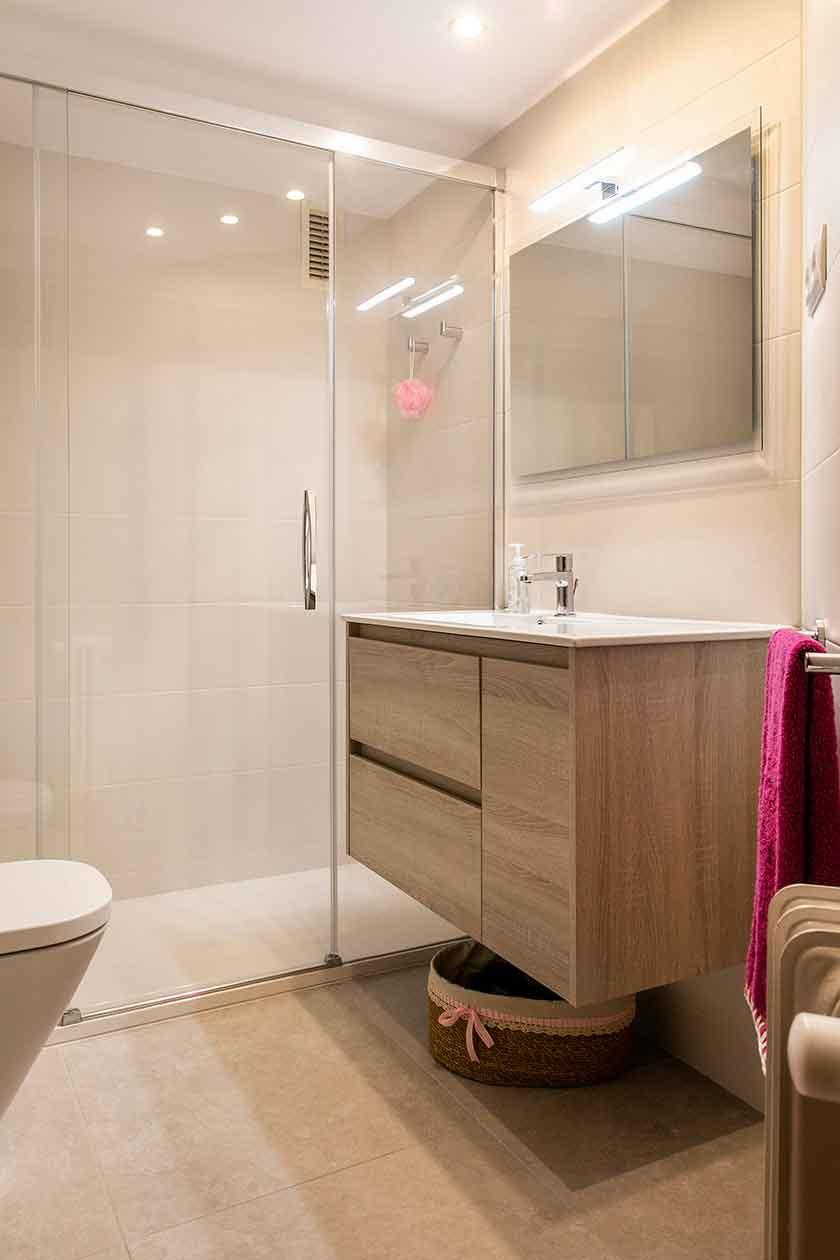 Vista general del baño reformado con el mueble y la ducha al fondo