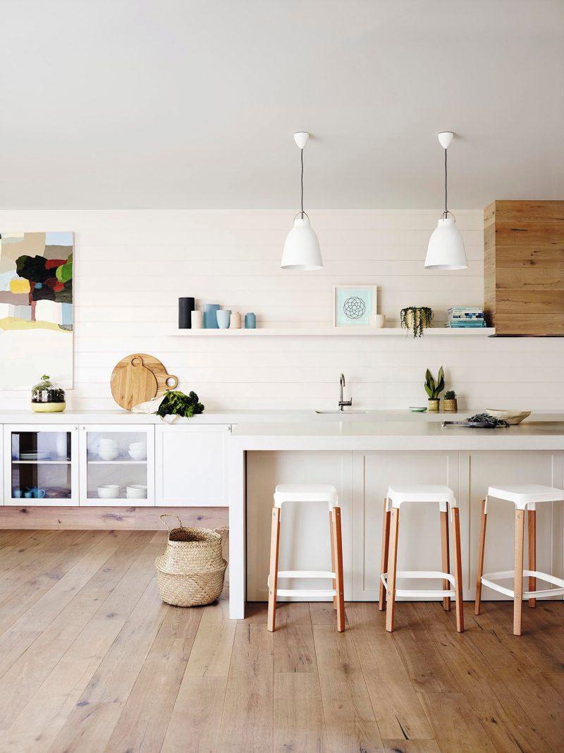 Cocina con isla y pared de lamas horizontales en tono blanco perlado y pavimento de lamas de madera