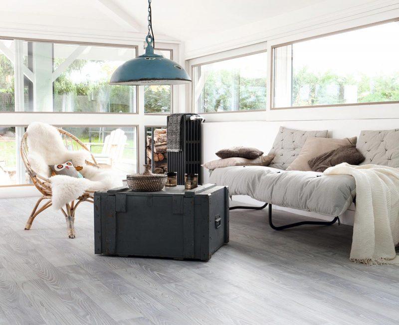 Salón de estilo nórdico con pavimento vinílico de lama ancha en tonos grises, para crear un juego de contrastes con las paredes en blanco impoluto