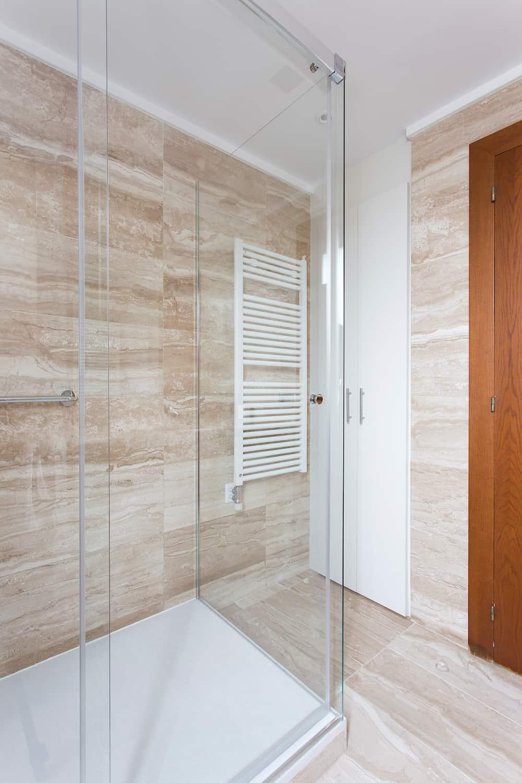 baño con mampara y puerta en madera